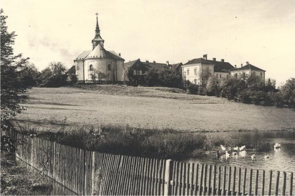 r. 1930 - zadní pohled na kostel, vpravo budovy tzv. Bílé a Červené školy.jpg